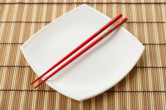Red Chopsticks And White Dish On A Bamboo Napkin Stock Photo