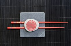 Red chopsticks on black bamboo Royalty Free Stock Photos