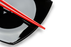 Red chopsticks on a black dish. Variant two. Royalty Free Stock Image
