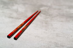 Red chopsticks on concrete background with selective focus royalty free stock images