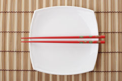 Red chopsticks and white dish on a bamboo napkin Royalty Free Stock Image