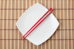 Red chopsticks and white dish on a bamboo napkin Stock Photos