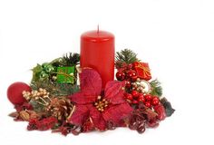 Red Christamas candle in poinsettia setting. With holly, evergreen branches isolated on white royalty free stock images