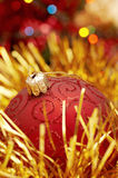 Red Christamas globe. Yellow bright tinsel and glowing lights in the background stock photos