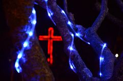 Red christian cross and blue led-lights. stock photography