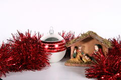 Red Christmas. A red glitter ball with a crib symbolizing Christmas. Isolated over white space (for text Stock Image