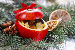 Red christmas apples stuffed with dried fruits in honey on fir b Stock Photo