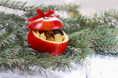 Red christmas apples stuffed with dried fruits in honey on fir b Stock Photos