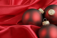 Red Christmas Background. Three red Christmas ornaments on red satin background stock photo