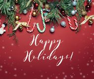 Red christmas Background with holiday decorations and Happy Holidays text royalty free stock image