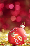 Red christmas ball. On abstract golden background stock photos
