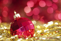 Red christmas ball. On abstract golden background stock images