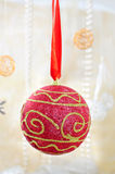 Red christmas ball. Red and gold christmas bauble on red ribbon Stock Image