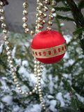 Red Christmas ball. Christmas tree under snow Stock Images