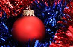 Red christmas ball. On a color tinsel Stock Image