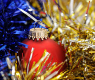 Red christmas ball. On a color tinsel Royalty Free Stock Photo