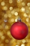 Red christmas ball against golden background Royalty Free Stock Photo