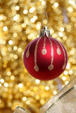 Red christmas ball against golden background. Red christmas ball against twinkling golden background Royalty Free Stock Image