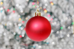 Red Christmas ball against silvery background. Of christmas lights Royalty Free Stock Photos