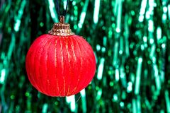 Red Christmas ball on a background of a green garland. Celebration stock image