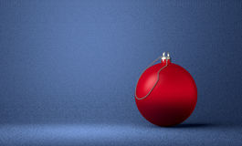 Red Christmas ball on blue background. Red Christmas ball on blue textured background Royalty Free Stock Image