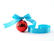 Close up single red glossy christmas ball with bright blue ribbon bow isolated on white background. Red glossy christmas ball with bright blue ribbon bow stock photography