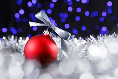 Red christmas ball and blured purple lights at the background Royalty Free Stock Photo