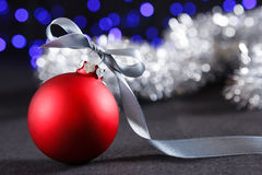 Red christmas ball and blured purple lights at the background Stock Images