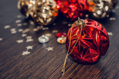 Red christmas ball on bokeh background of xmas ornaments. Stock Photos