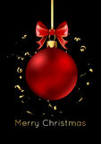 Red Christmas ball with a bow, isolated on black background. Stock Photo