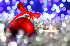 Red christmas ball and candle, blured purple lights at the background Royalty Free Stock Photos