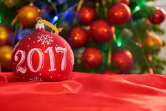 Red Christmas ball on the Christmas tree. Red Christmas ball 2017 on the Christmas tree Stock Photo