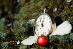 Red christmas ball and clock on a spruce. Stock Photography
