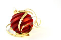 Red Christmas ball with curly ribbons on white Royalty Free Stock Photos