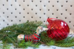 Red Christmas ball and dachshund in red-green sweater on branch of Christmas tree. On white background royalty free stock photography