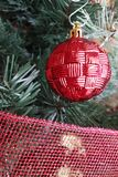 Red Christmas ball decoration. Hanging on a Christmas tree with some red ribbon Stock Photos