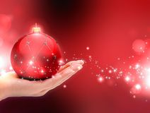 Red Christmas ball on female hands. Stock Photo