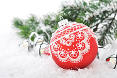Red christmas ball. And fir branches with decorations on snow Stock Image