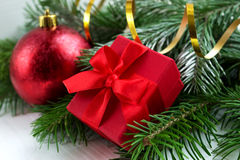 Red christmas ball and gift wih fir branches Royalty Free Stock Image