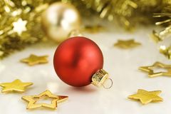 Red Christmas ball and gold stars. Royalty Free Stock Image