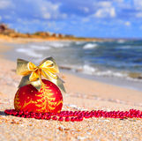 Red christmas ball with golden bow on the sand Royalty Free Stock Image