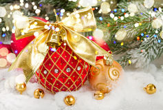 Red christmas ball with golden bow in snow Stock Photography