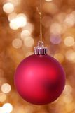 Red Christmas Ball with Golden Glittering Background. Red Christmas Ball Against Unfocused Golden Glittering Background Stock Photo
