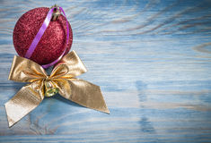 Red Christmas ball golden knot on wooden board holidays concept Royalty Free Stock Photo
