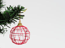 Red Christmas ball hanged on green christmas pine tree branch on white background. Red Christmas ball with gold ribbon hanged on green christmas pine tree branch stock photos