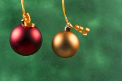 red christmas ball hanging with orange ribbon on green background stock images