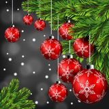 Red christmas ball hanging on pine leaves in winter night background Stock Photo