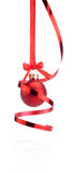 Red Christmas ball hanging with ribbon bow and curling paper. Isolated on white background stock photography