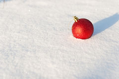 Red Christmas ball. Lies on white snow Stock Images