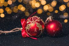 Red christmas ball on light abstract background. Christmas greeting card. Snow effects. Soft focus royalty free stock images